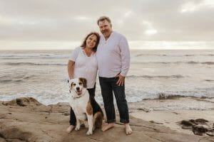 Couple and dog standing on rocks in front of ocean with overcast sky