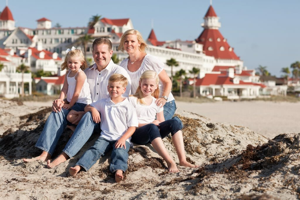 Happy Caucasian Family in Front of Hotel Del Coronado, U.S.A., on a Sunny Afternoon.