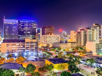 Lights from the towering buildings glow in the night at the streets buzz with light and activity in downtown San Diego