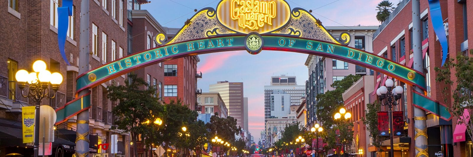 As the sun sets, cars zoom underneath the lit sign reading Gaslamp District in San Diego, California