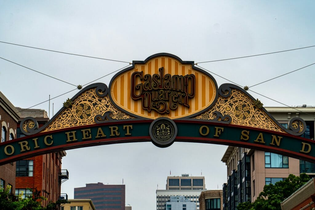 Sign of the Gaslamp Quarter at a close up with a gloomy sky as the background with building peaking up at the bottom