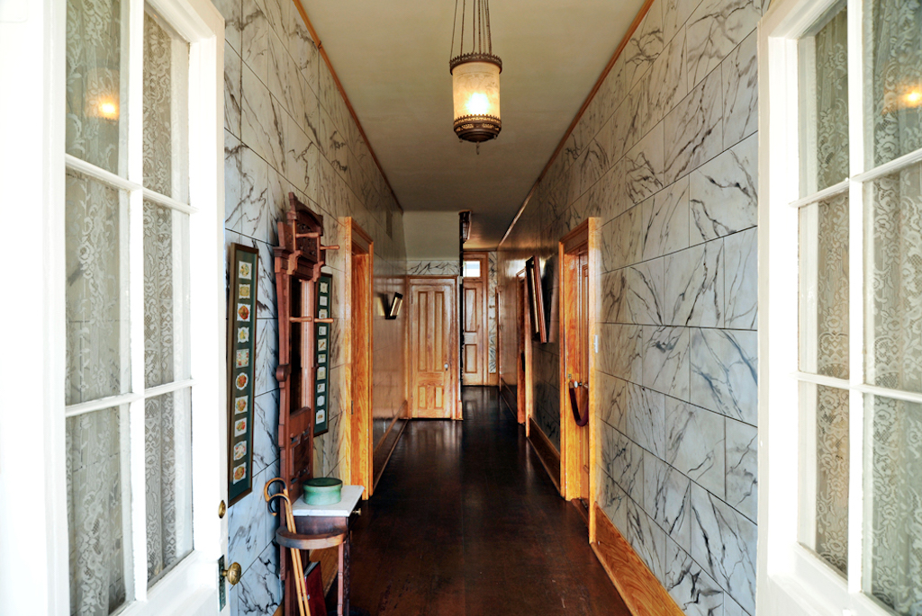 A long marble entry way hall with lights and light wood adornments