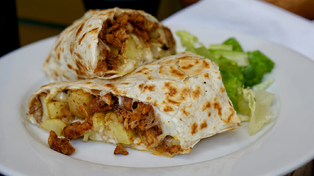 Two halves of a burrito with one on top and one of the bottom filled with chicken, potatoes, guac, and sour cream
