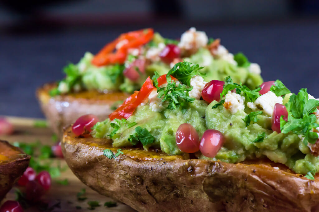 Baked sweet potatoes with guacamole, feta cheese and pomegranate