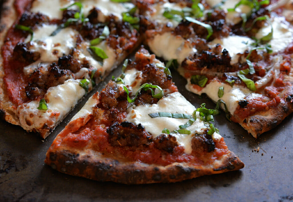 Closeup of artisanal wood fired pizza with sausage, mozzarella and basil