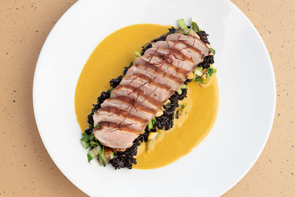 In a pool of silky yellow sauce, a perfect duck breast is slices and places over greens on a white round plate