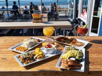 Several plates filled with breakfast foods near glasses of mimosas are displayed on a table with more chairs and the beach in the background