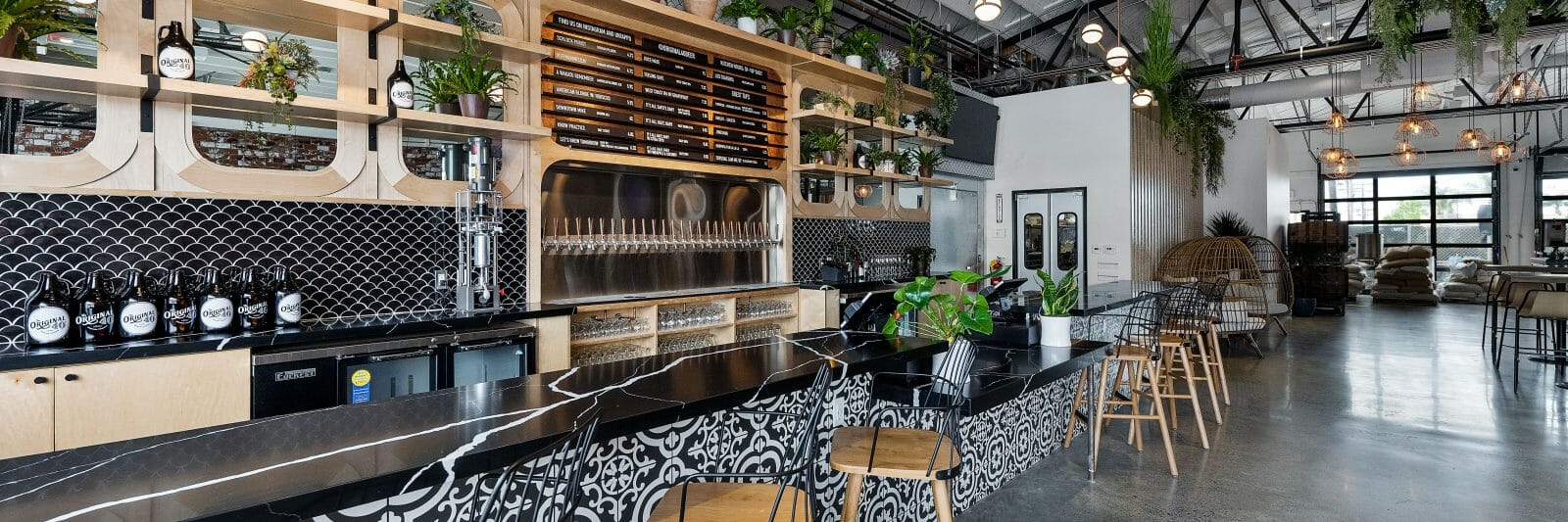Modern Bar in restaurant. Plants line the walls of the bar, beer is tapped up to the levers and the seats are empty and awaiting guests