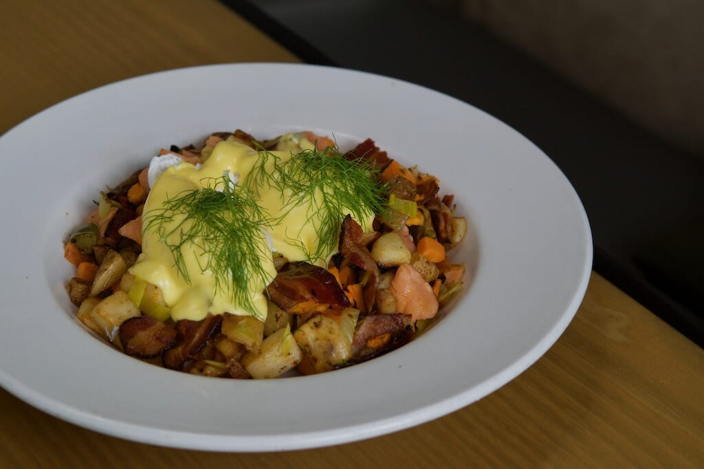 A bowl of potato hash is topped with two poached eggs, velvety hollandaise, and dill