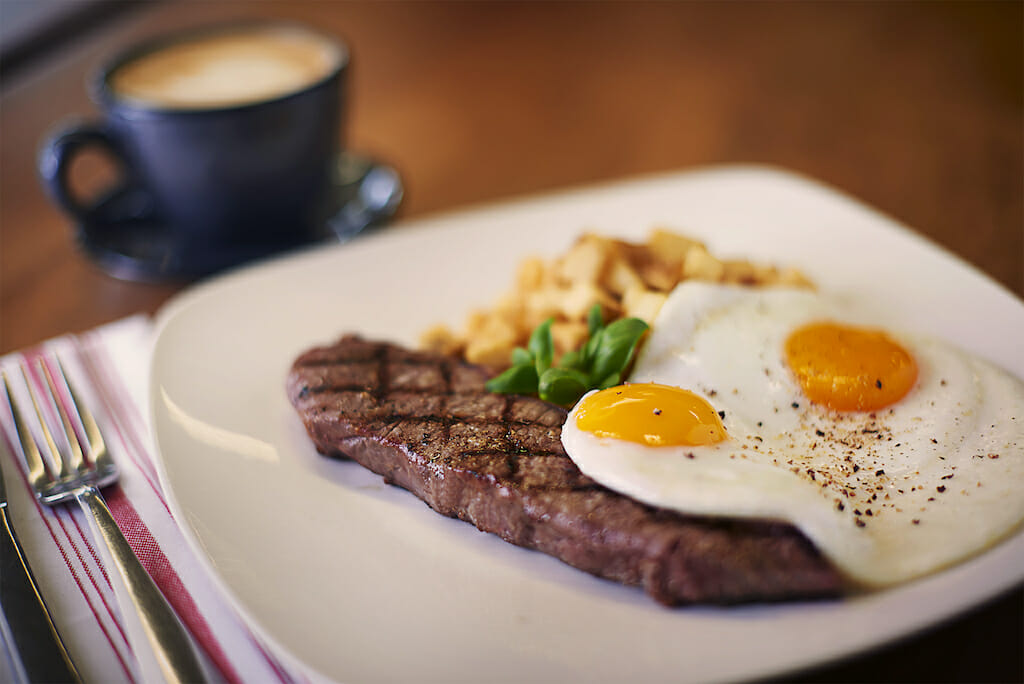 A slab of steak laying under two perfectly cooked sunnyside up eggs on a plate with a coffee behind it