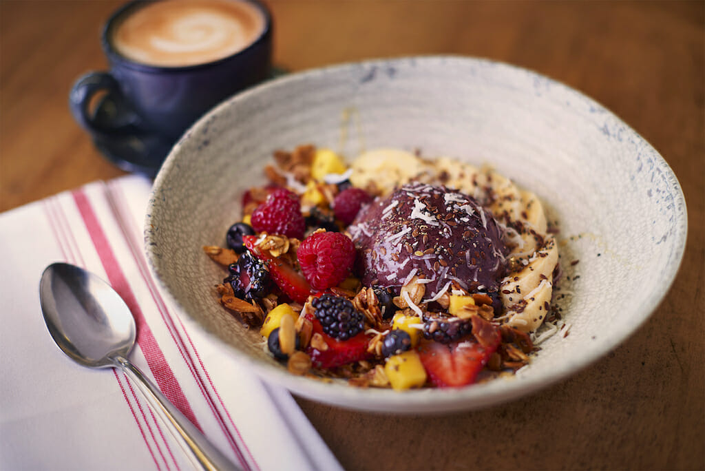 A bowl filled with blended acai with oats and fruits with coffee behind it