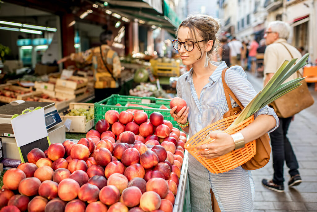 Young woman choosing a fresh peach standing with basket at the food market in France
