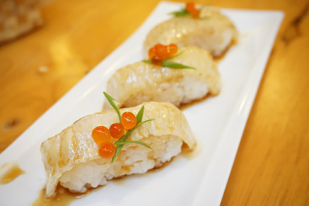 Aburi engawa sushi - Grilled flatfish (Fluke fin) on rice topping with salmon roe (Ikura) served with wasabi and pickled ginger, Japanese traditional food.