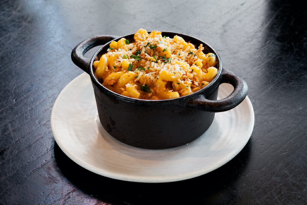 Gourmet mac and cheese with breadcrumbs served in a black pot on a dark table.