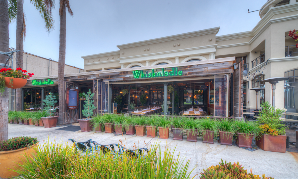 The outside of a restaurant with a green sign and greenery all around