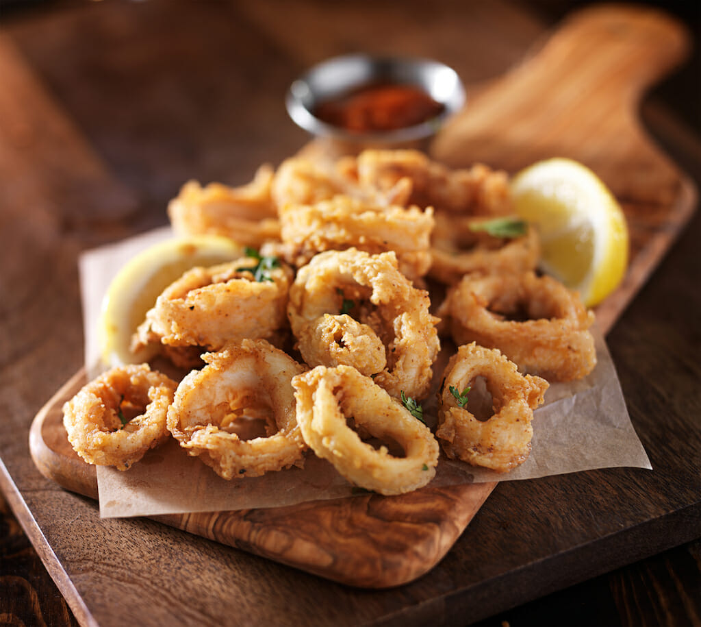 fried calamari squid appetizer on wooden serving tray