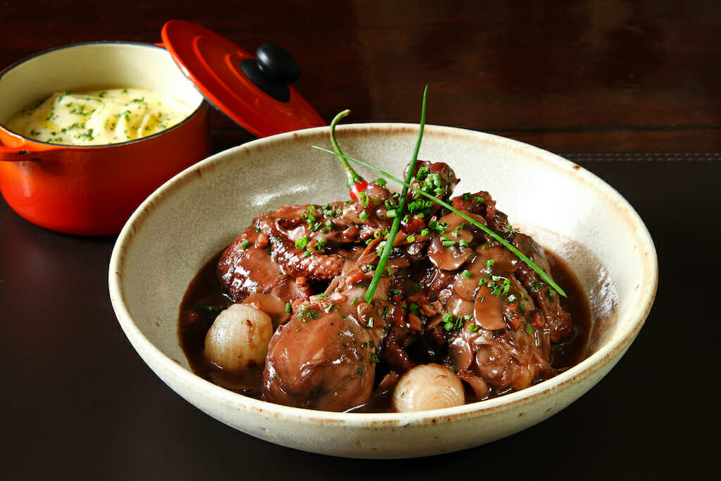 Classic coq au vin with a pot of mashed potatoes behind it