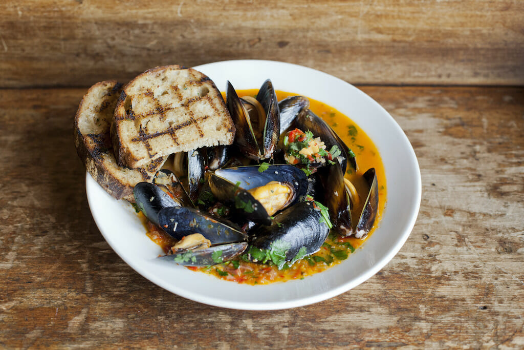 Two pieces of toast placed on the side of a bowl of mussels in a colorful broth