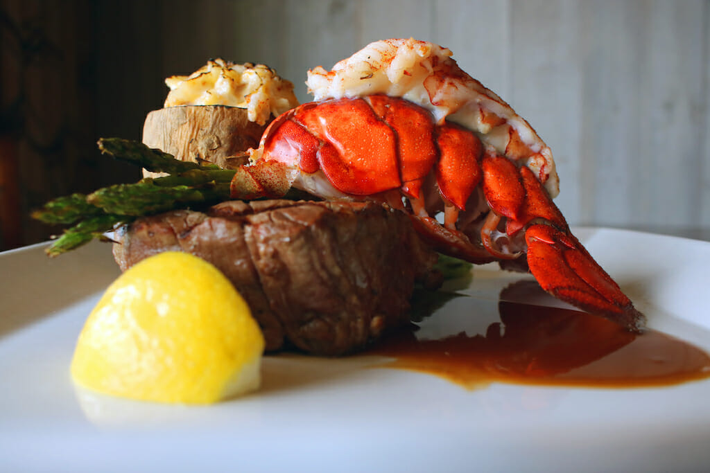 A filet resting behind a wedge of lemon with a lobster tail laying on top