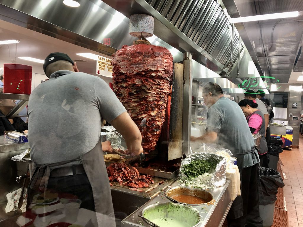 Adobada/Al Pastor tacos roasted on a spit at Tacos El Gordo with man cutting of thin slices