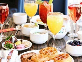 Best Brunch in San Diego - Table with brunch dishes like fruit, waffles, mimosas, coffee, and other drinks.