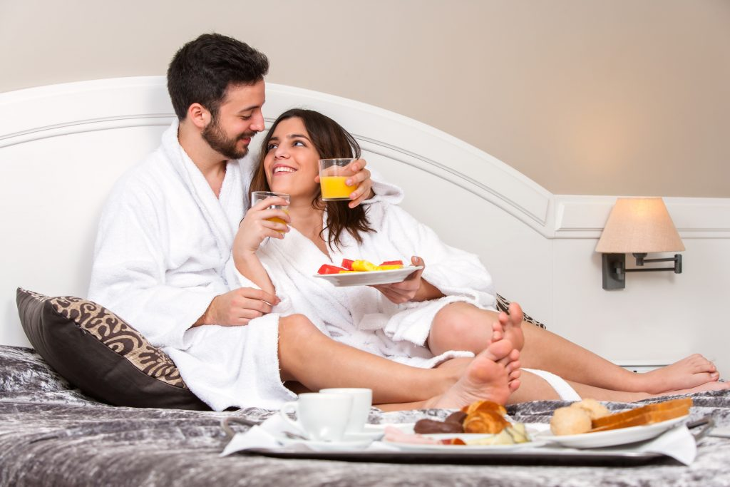Close up portrait of Young couple on honeymoon in hotel room. Couple enjoying room service with breakfast tray.