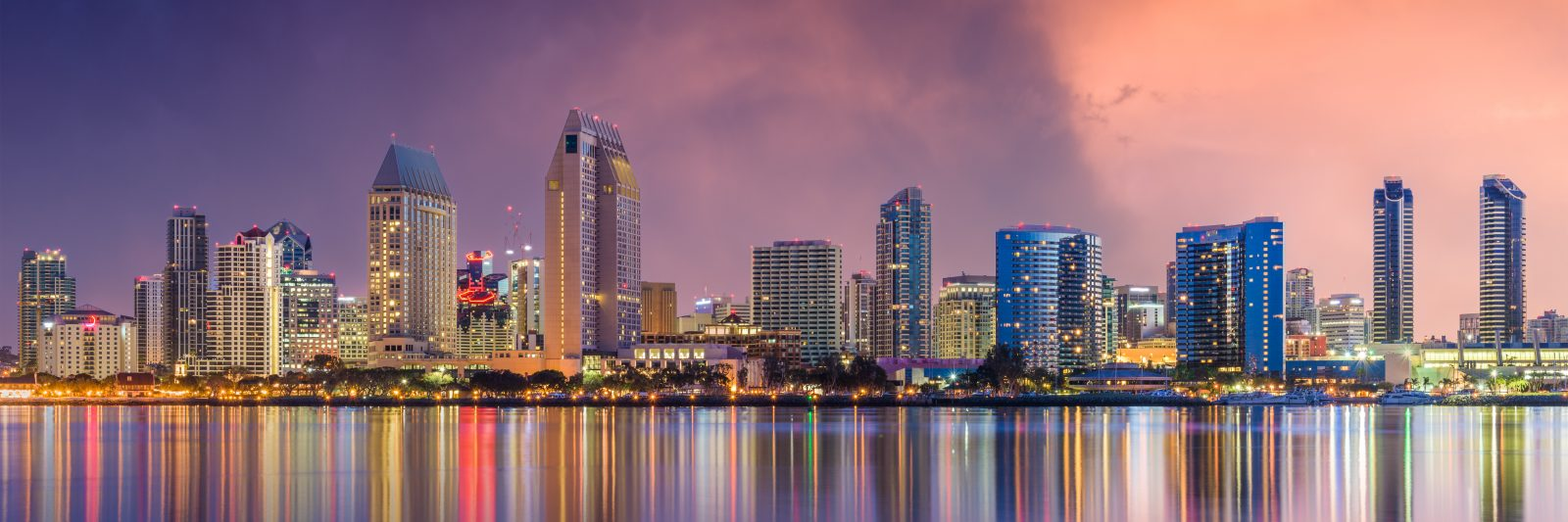 San Diego Skyline reflecting in the water at sunset with purple and pink sky