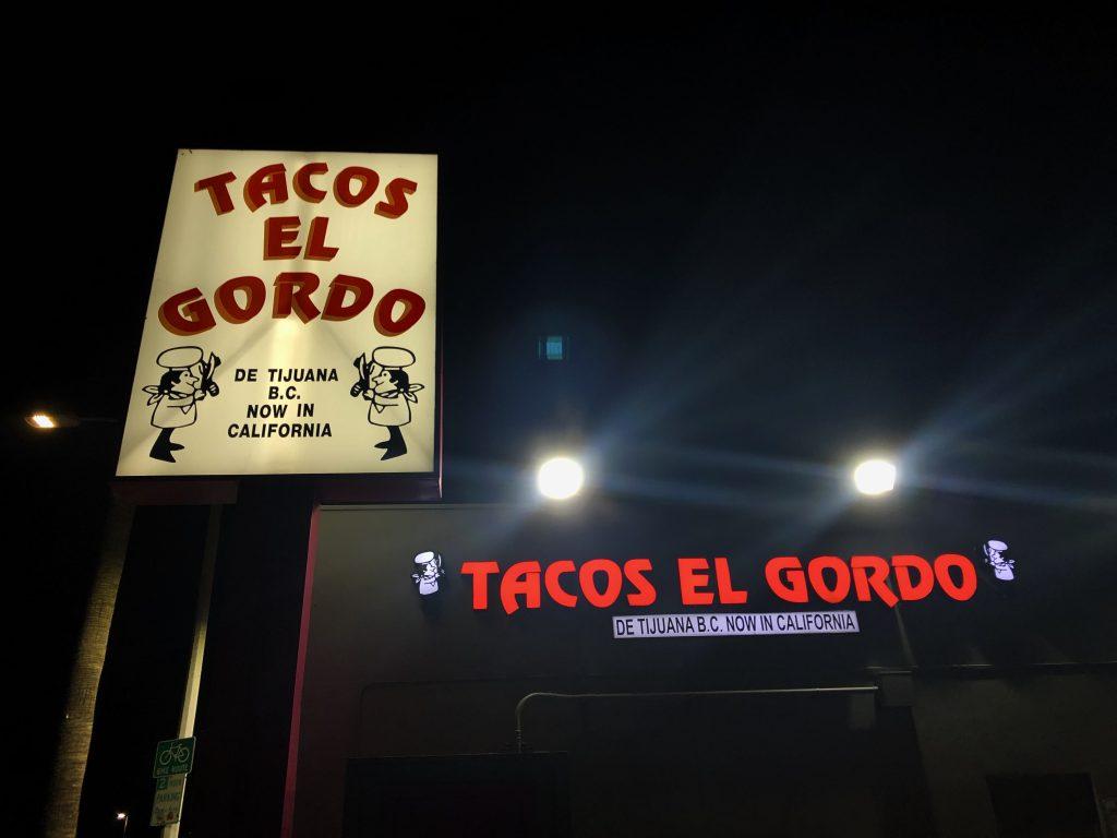 Restaurant Sign of Tacos El Gordo lid up at night