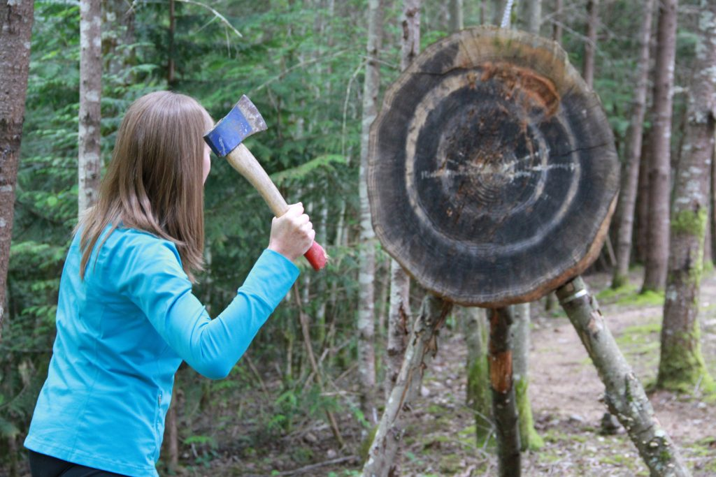 Woman in blue shirt in the forest throwing an axe towards a wood target