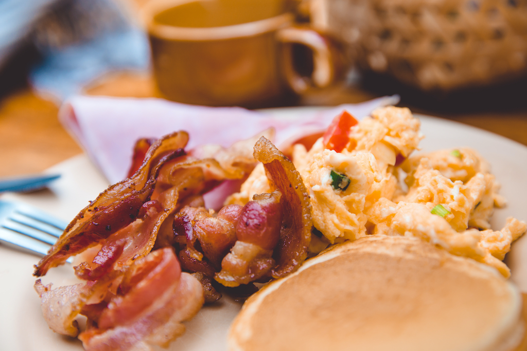 A pile of fresh bacon next to a stack of pancakes and a pile of eggs with coffee nearby