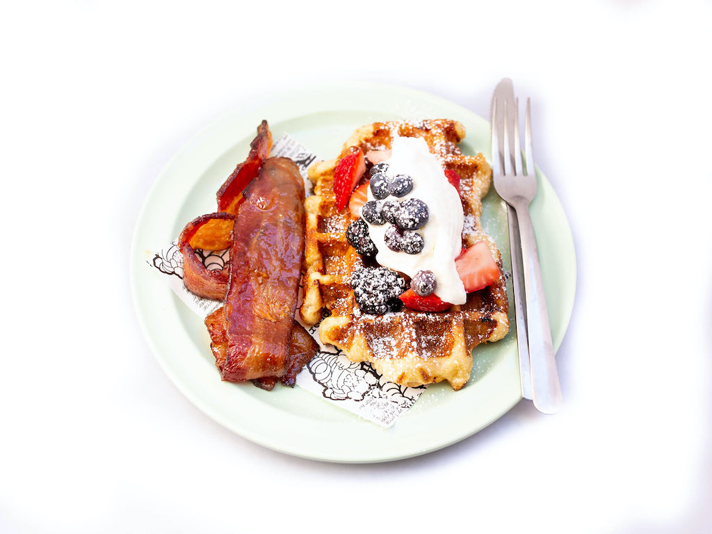 A waffle with whipped cream, strawberries, and blueberries on top with bacon on the side