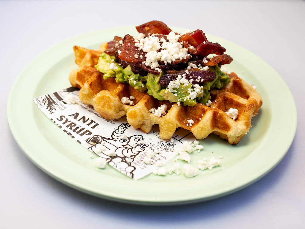 Waffle with guacamole, bacon, and cheese on top