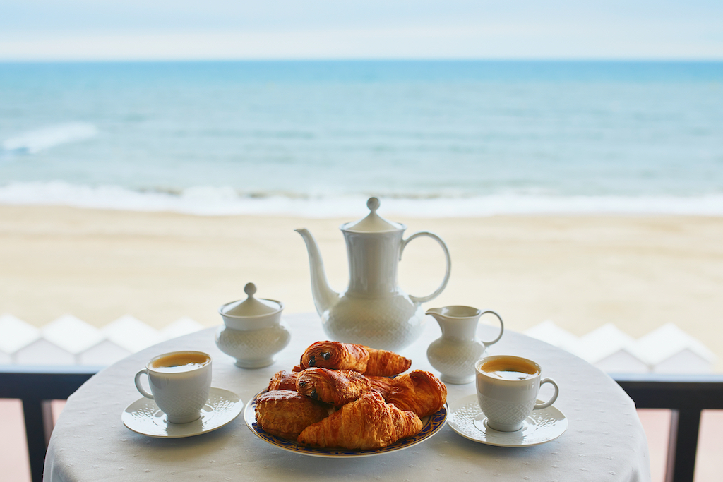 Two cups of coffee and traditional French pastry in cafe or restaurant with a view. Breakfast on balcony near sea or ocean