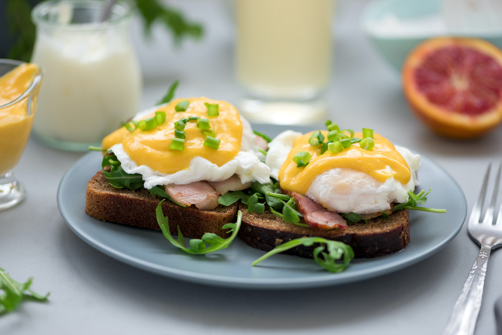Close up eggs Benedict with arugula, becon and hollandaise sauce on gray wooden background. Soft focus. Healthy eating concept