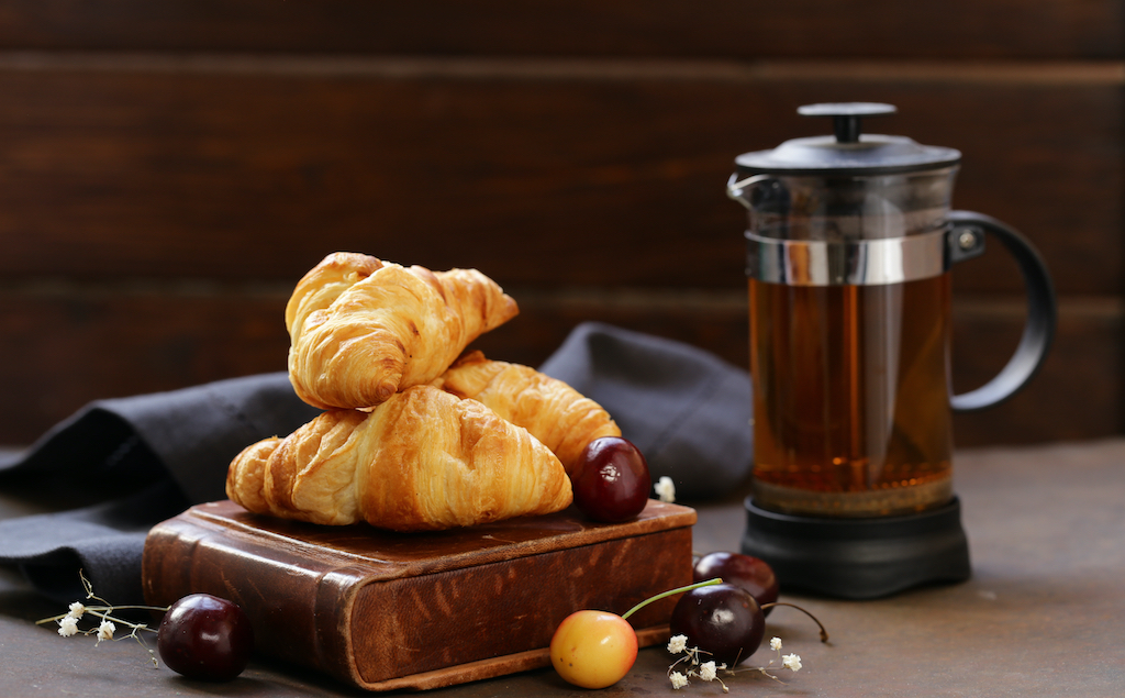 Three croissants on a wooden stand next to a pitcher of French press coffee