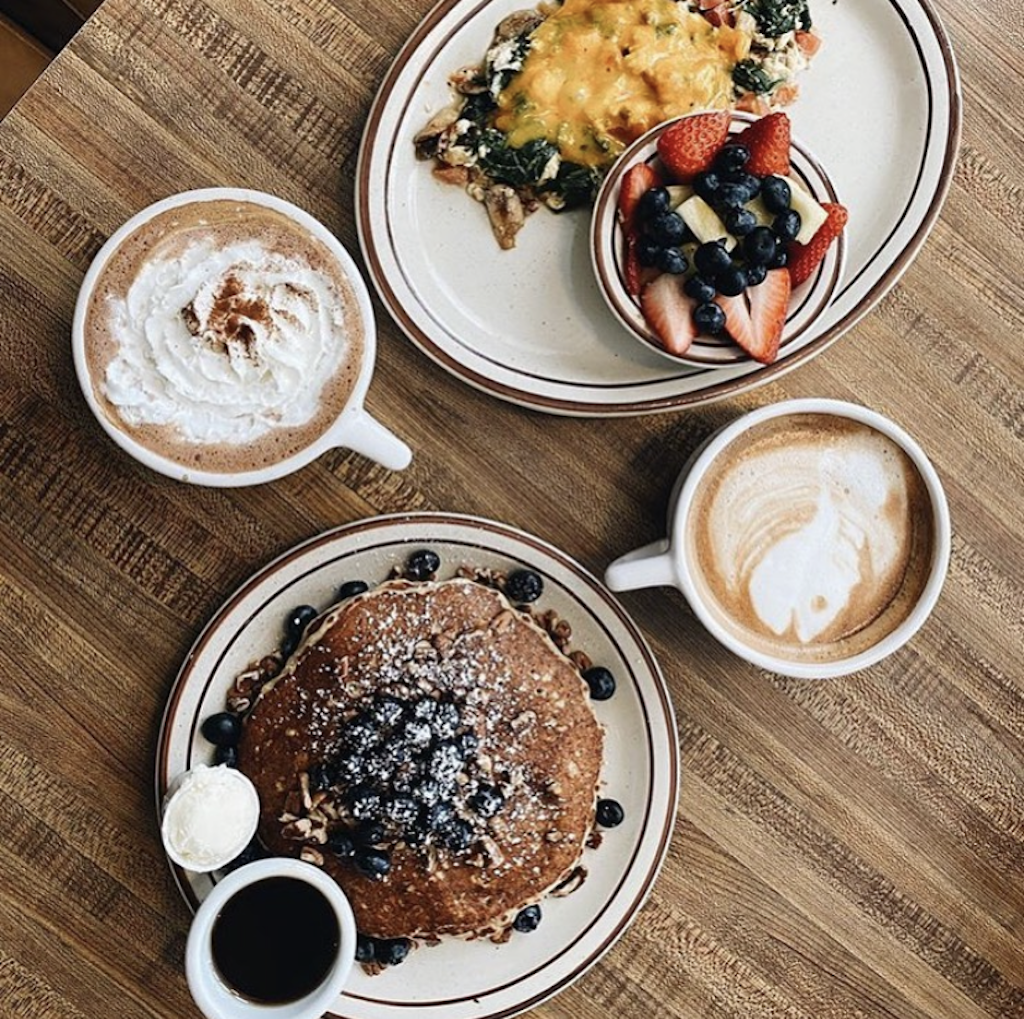 A table with a plate of chocolate pancakes with syrup, two coffees, and a hash with a side of fruit