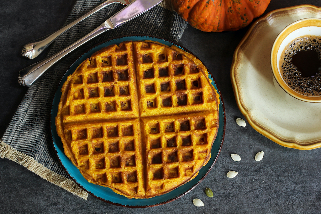 A stack of pumpkin waffles  next to a cup of coffee