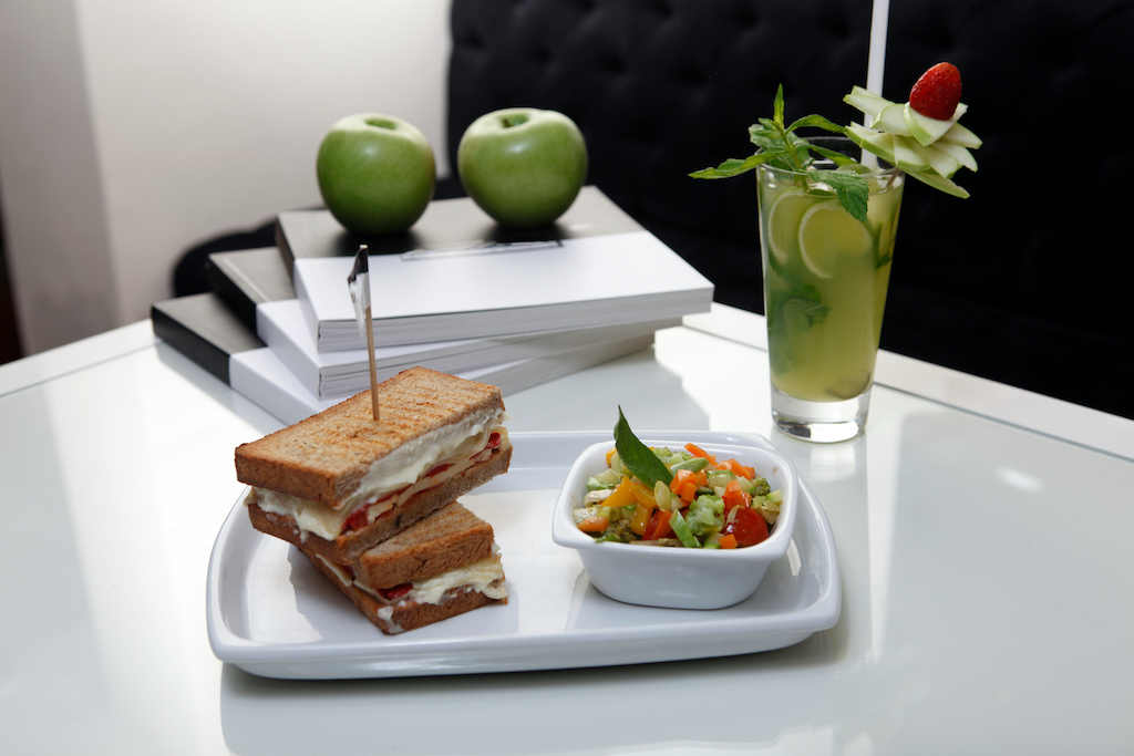 A toasted sandwich on a white plate next to  a bowl of healthy fruit salad and a morning cocktail