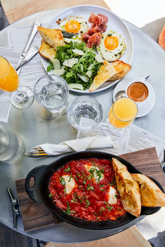 Two breakfast dishes, one with tomato sauce and bread and the other with veggies and two eggs
