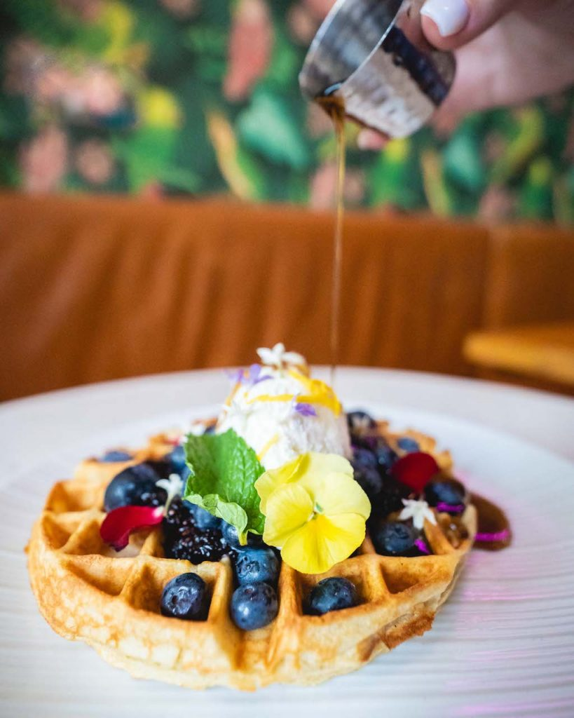 A waffle topped with an abundance of berries and edible flowers has syrup being poured over it delicately