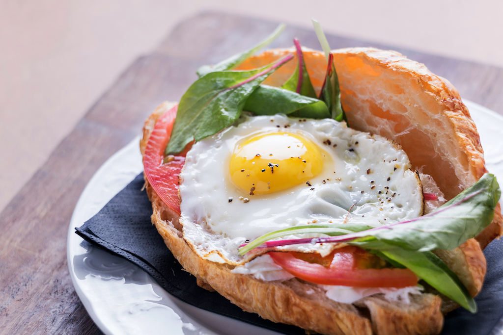 Croissant sandwich with salmon, arugala, and a sunny side up egg