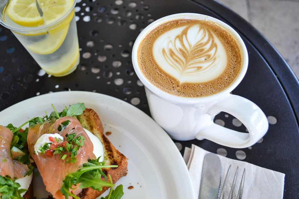 Salmon tops crunchy toast, served with fancy coffee...cappuccino with design in the foam. Eating raw and and natural in an outdoor cafe enhances your lifestyle choice for healthy living