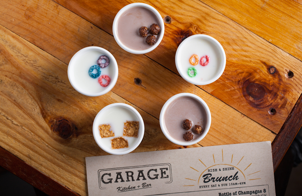 Five shot glasses filled with liquor and different cereals arranged in a pentagon