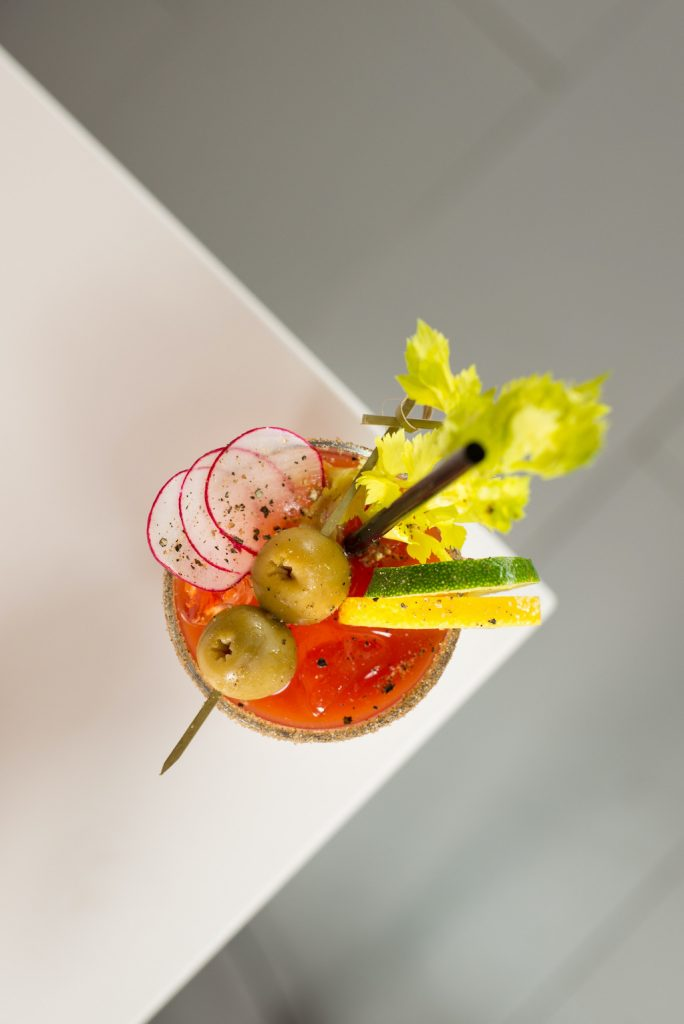 Overhead shot of a bloody mary drink with olives, celery, squash, and radishes