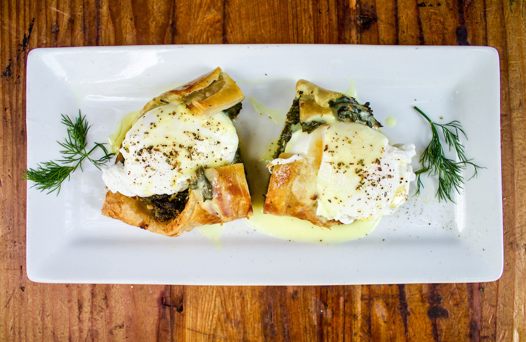 Eggs benedict with spanakopita on top under the poached eggs