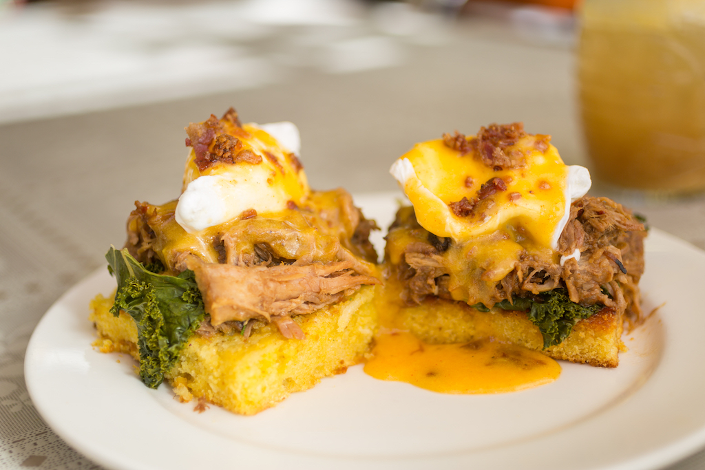 An eggs benedict on a sweet roll with pork and greens
