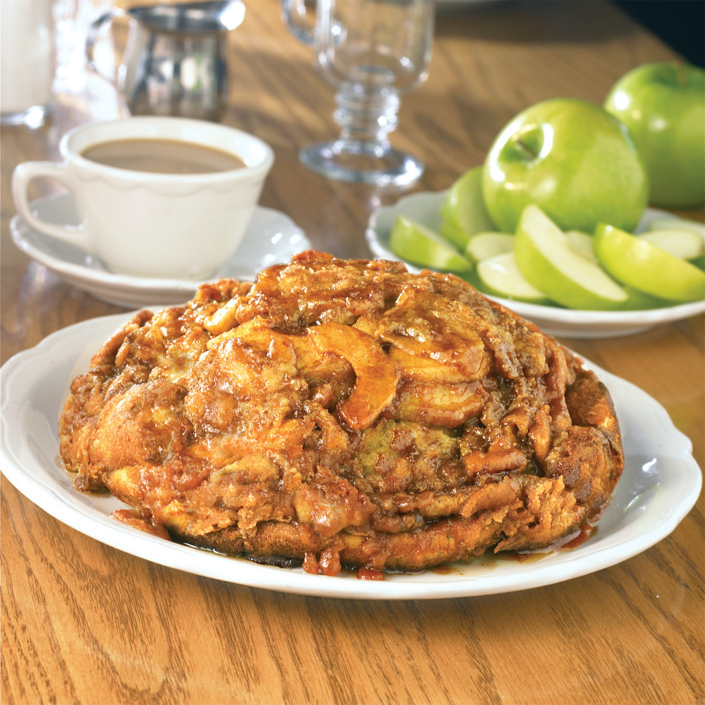 A big lump of a pancake filled with apples and sugar laid on a plate near coffee and whole apples