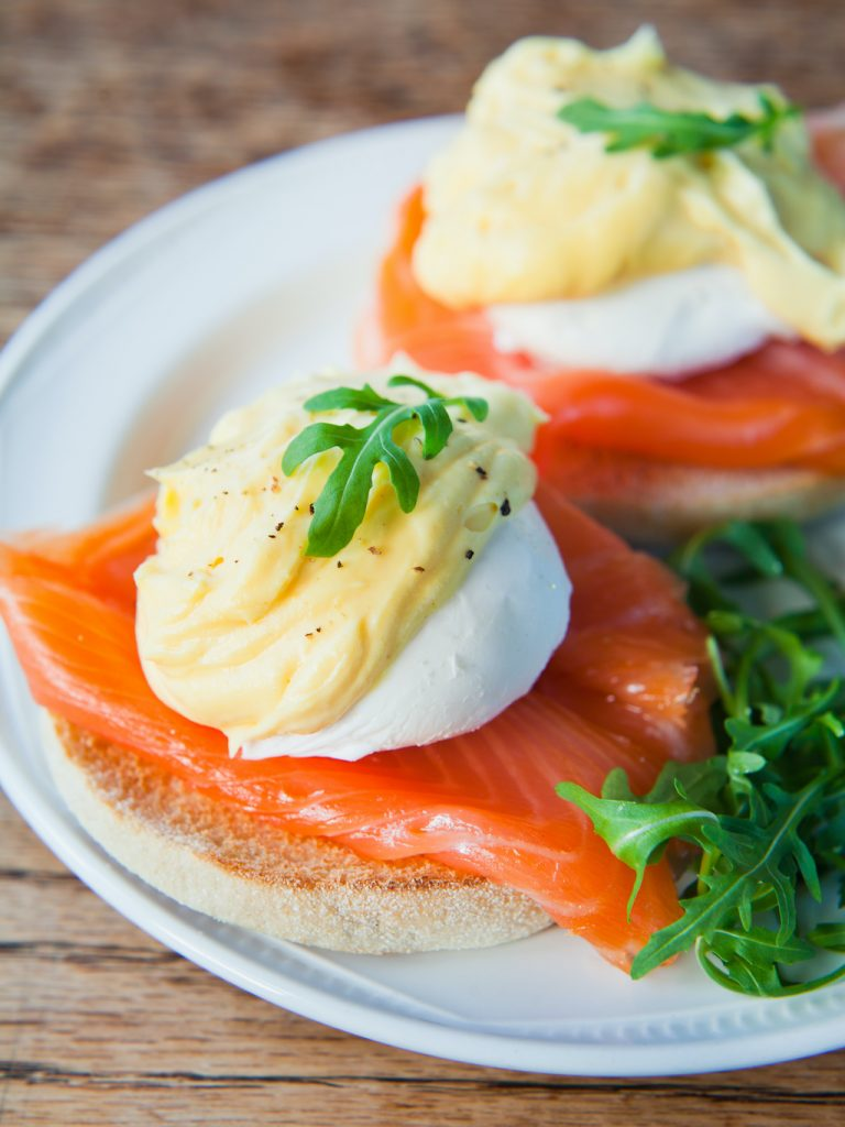 Eggs Benedict - Poached eggs with Hollandaise Sauce, fresh arugula and Smoked Salmon on English Muffin. Perfect Breakfast or lunch.