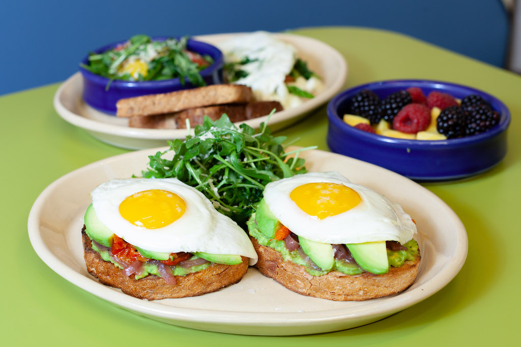 Avocado toast with two sunny side up eggs and tomato