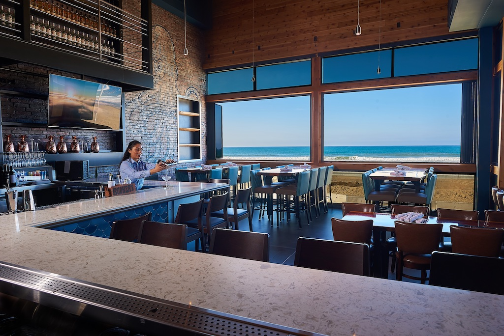 A gorgeous view of the beach out the window of a modern bar